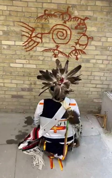 Thomas Sinclair kneeling in full regalia in front of a painting he created on the Royal Ontario Museum walls