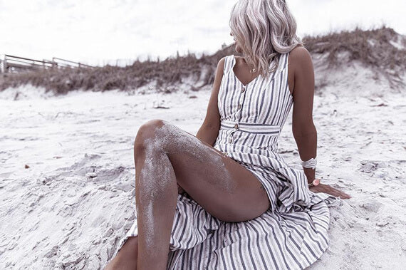 girl in a button front striped dress sitting on a sand beach looking away from the camera