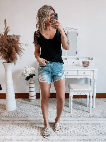 woman modeling a black lace sleeve tee and denim shorts