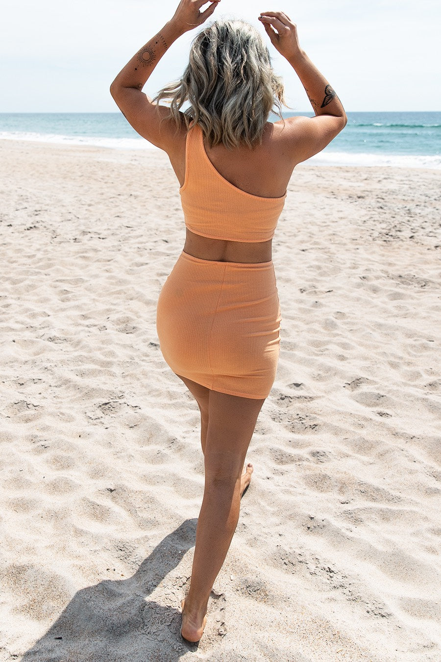 woman waling on a white sand beach in a peach cutout dress