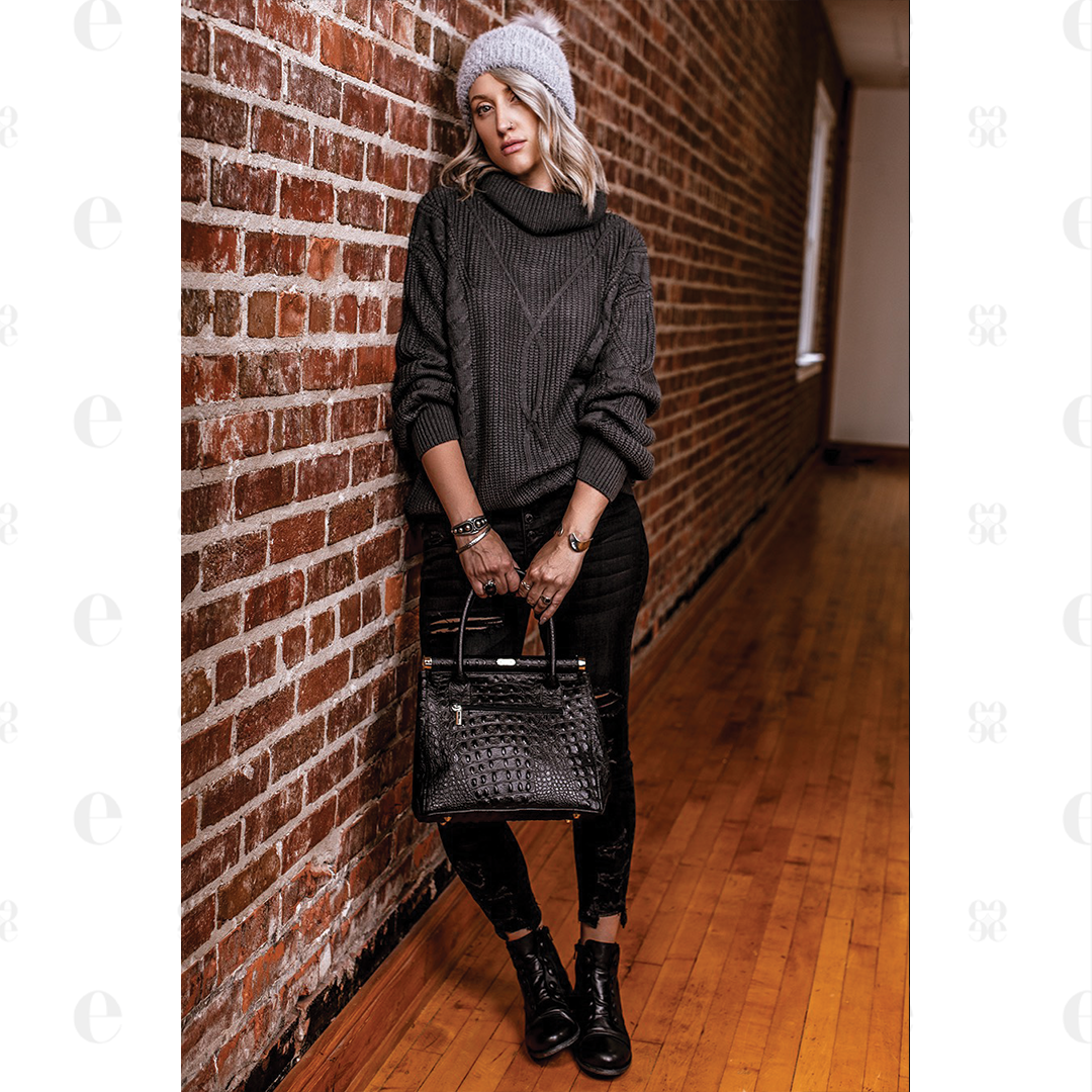 women in grey cable knit chunky sweater with black jeans grey beanie black leather shoes and black leather purse