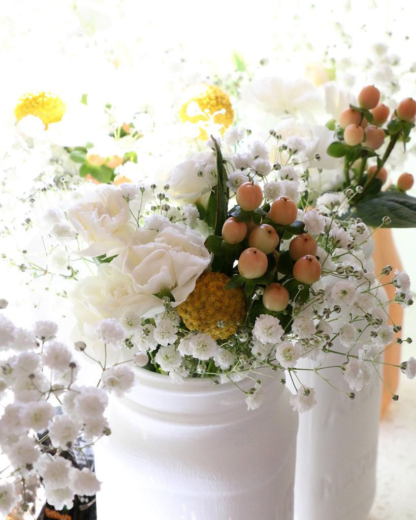 floral centerpieces, peach hypericum, babys breath, roses, mini carnations
