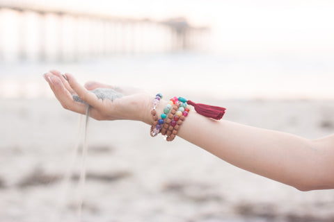 The Mala Babe rainbow mala wrapped around the wrist holding sand