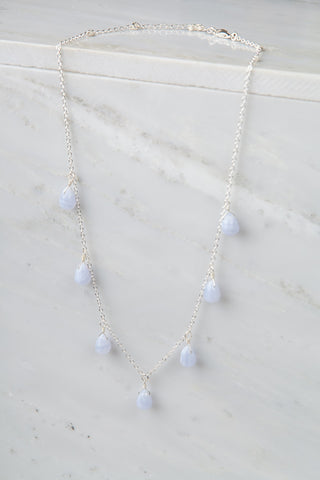 The Mala Babe Necklace with many blue lace agate drops on marble