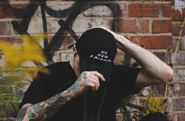 Tattooed model against brick wall wearing a black six panel dad hat with white embroidery that says No New Friends. Features an adjustable back strap with brass buckle. Made by Toronto clothing company Shook Co.