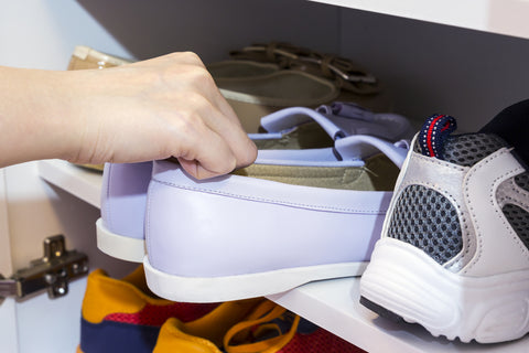 Young woman pulling out pair of shoes from cabinet