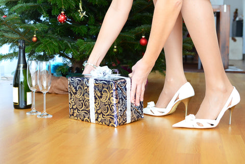 A lady wearing heels picking up a present under Christmas Tree