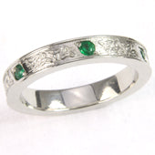 A platinum wedding ring encrusted with celtic love knots and emeralds.