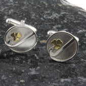 A pair of silver sterling cufflinks with a golden trefoil