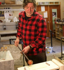 Scott Benefield is a world expert in glass blowing, this image is a portrait of the artist at work