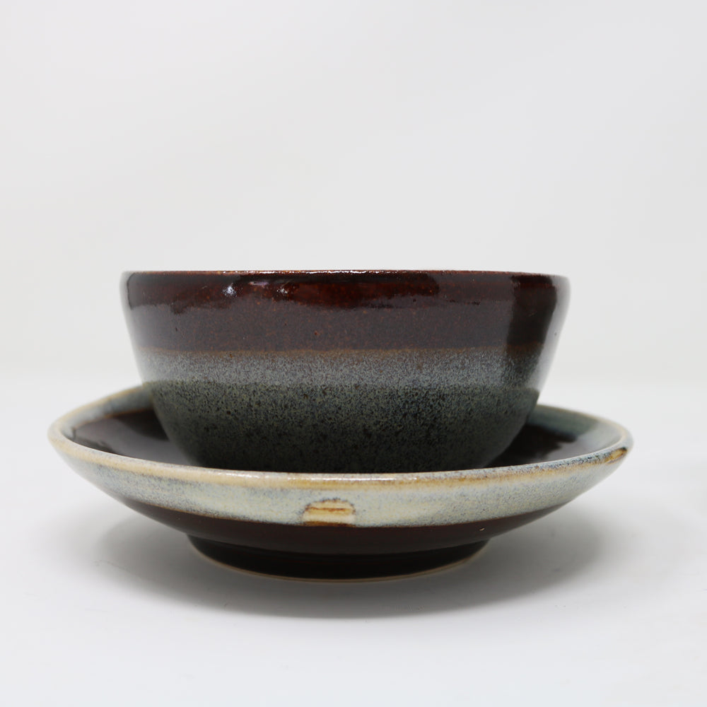Large coffee cup with a dark brown top and blue grey body glaze, shaped as a lily leaf, signature shape of Claire Murdock's ceramics. The cup comes with a matching saucer.