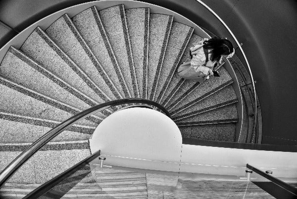 Abstract black and white photograph taken at Victoria Square, Belfast, Northern Ireland.   Shown is a spiral staircase with Korean tourist in beautiful Fibonacci spiral composition.