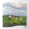 Irish landscape rendered in felt wool by talented felt artist Louisa Kelly. Cloudy sky in blue, pink, white and grey over an Irish cottage, green hills and sheep.
