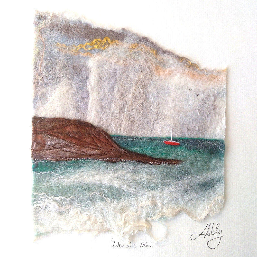 Seascape with a red boat sailing in a turquoise sea with brown cliff and rain approaching in the background - the sky has yellow, orange, pink and grey colours. Felt art by Louisa Kelly.