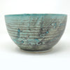 Medium large bowl with a greenish light grey background and turquoise blue green splashes of glaze on the outside. This is a side view.