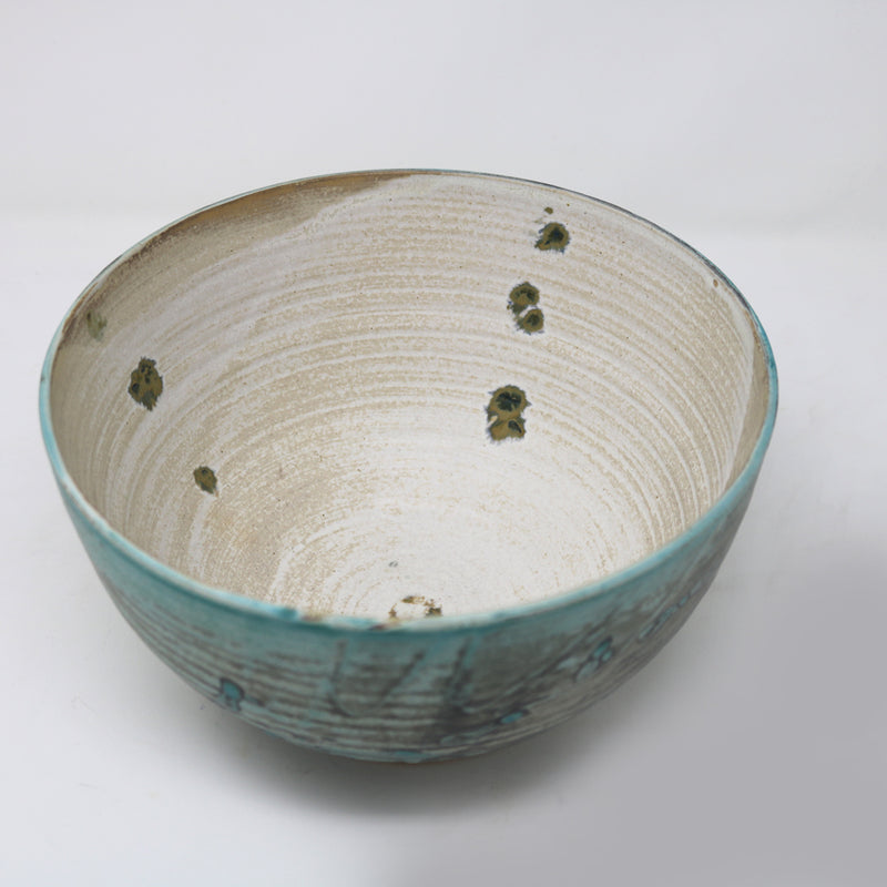 A different foodsafe glaze is used for the inside of the bowl. The colour is cream white with a few hints of the peacock green and blue glaze. Perfect for holding fruit or as a contemporary craft decorative piece.