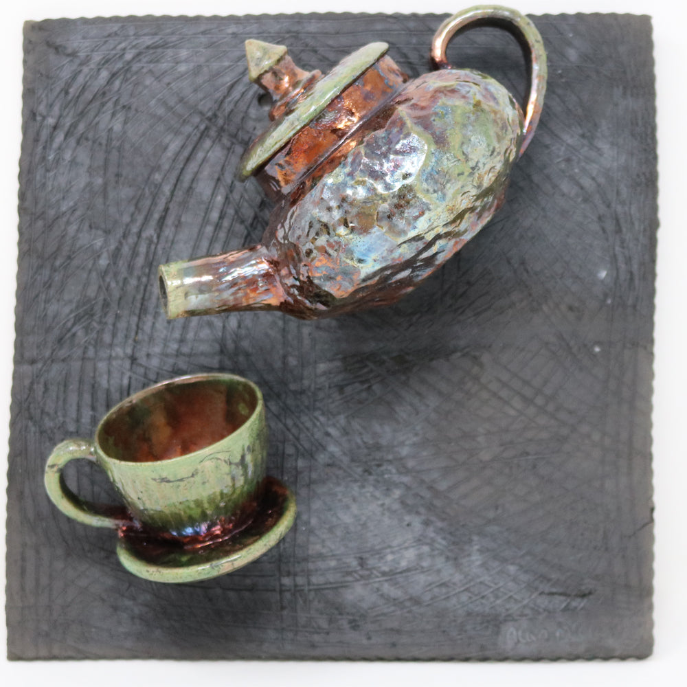 A teapot stuck on a charcoal grey slate tile with a cup and saucer. Raku ceramic piece with beautiful copper and green colours. Unique contemporary craft ceramics handmade in Ireland.
