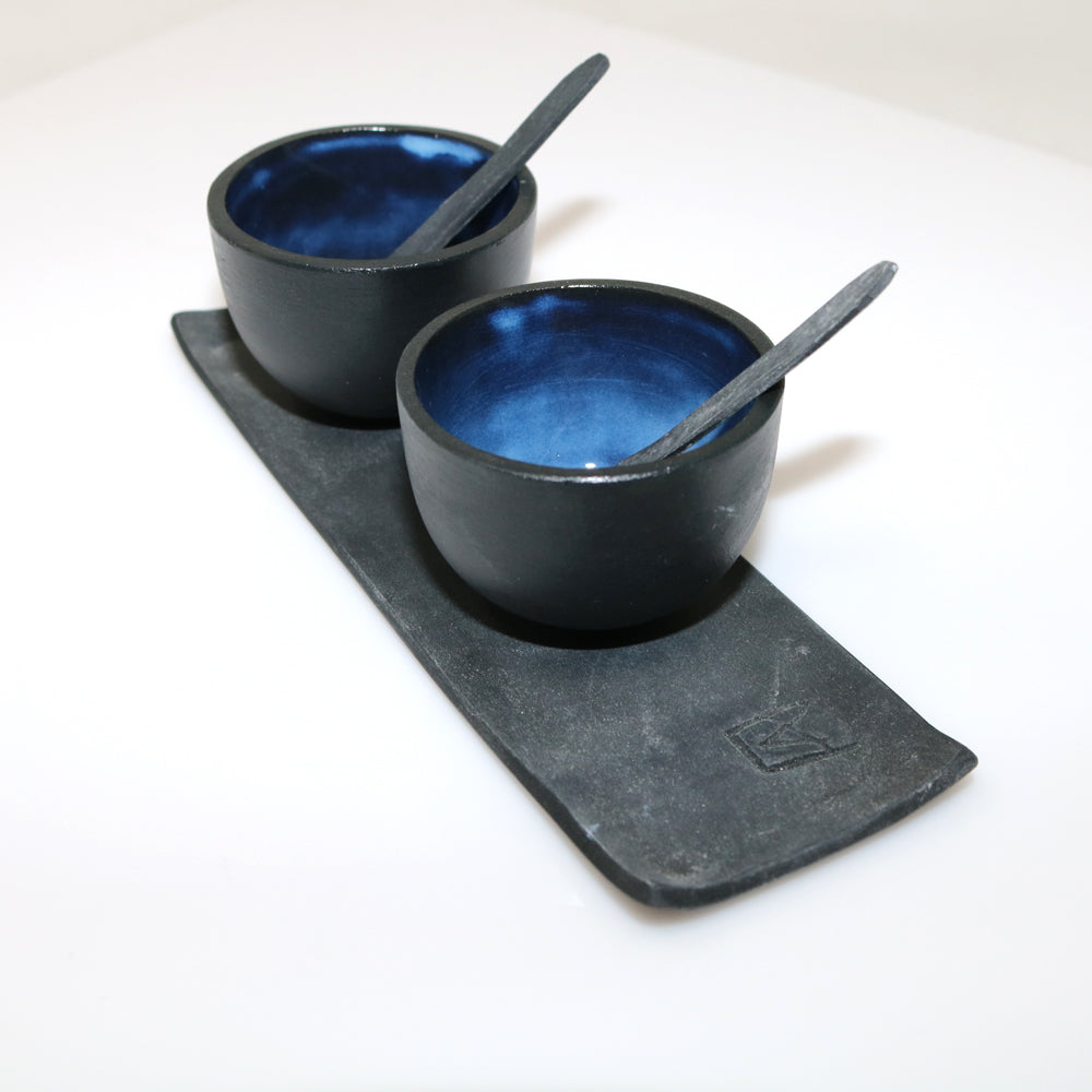 hand made ceramic salt and pepper set, materials used is Parian China a very fine type of porcelain. Each tiny bowl is hand made, decorated and glazed inside with a deep blue shiny glaze and a charcoal grey/black matt glaze on the outside. The small grey dish is stamped with Anne Butler's signature. A beautiful dainty salt and pepper set to treasure.