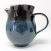 Small milk jug which can be part of a complete expresso service or used as a standalone. Made by Claire Murdock, the glaze on the cup is dark blue with lighter blue specks with a dark reddish brown top.