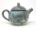 This beautiful round shaped turquoise green and blue teapot on a grey background is part of Alan McCluney's collection. We love the large handle which makes pouring agreable. The lid of the teapot has a small dome similar to the one on Mussenden temple.