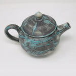 Turquoise, green, blue on a light grey background, this teapot is a nice piece of Irish contemporary craft.
