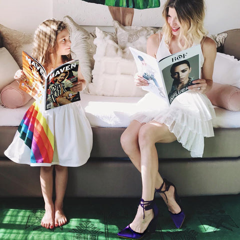 A mom and daughter smiling at each other while reading magazines