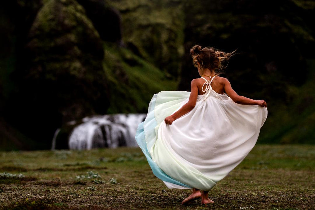 child dancing in Iceland wearing the sea glass Stella. pleiades designs and the traveling dress collective