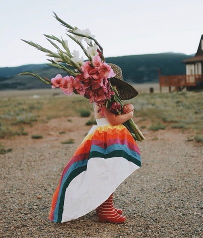 A child wearing the classic rainbow high low while holding a big bouquet of flowers over her face