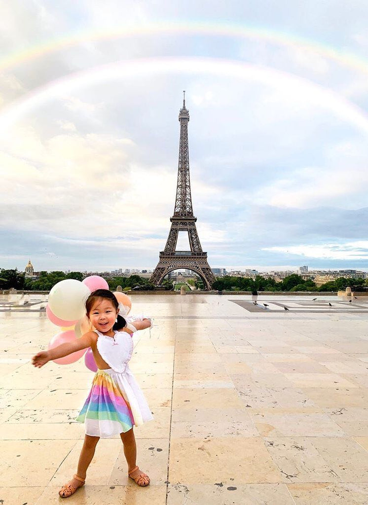 A child wearing the pastel penny in front of the Eiffel Tower