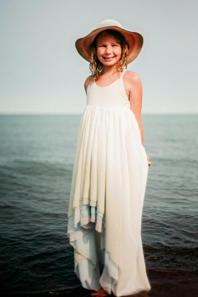 child at the beach wearing the sea glass Stella. pleiades designs and the traveling dress collective