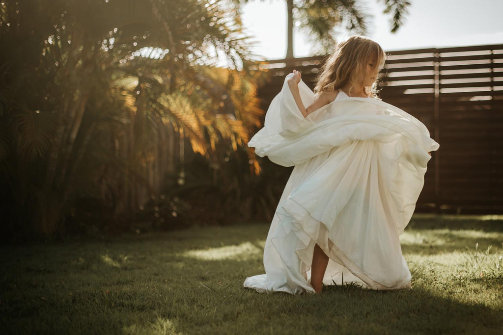 a child dancing at dawn wearing the sea glass Stella dress. Pleaides Designs and the traveling dress collective