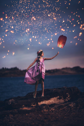 a child wearing the rapunzel dress with a bunch of floating lights behind her
