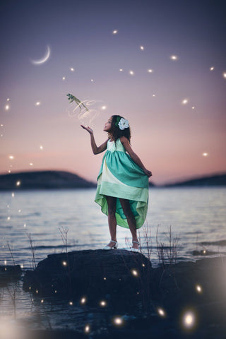 A child wearing the Tiana dress letting a frog jump from her hand with the stars shining in the background