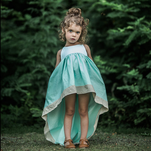 a moody child wearing the mint windsong in front of an emerald green tree line