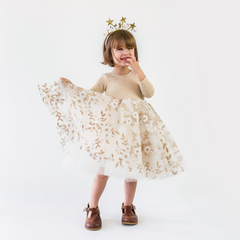 A child posing wearing the gold tinsel tulle dress with a gold star headpiece