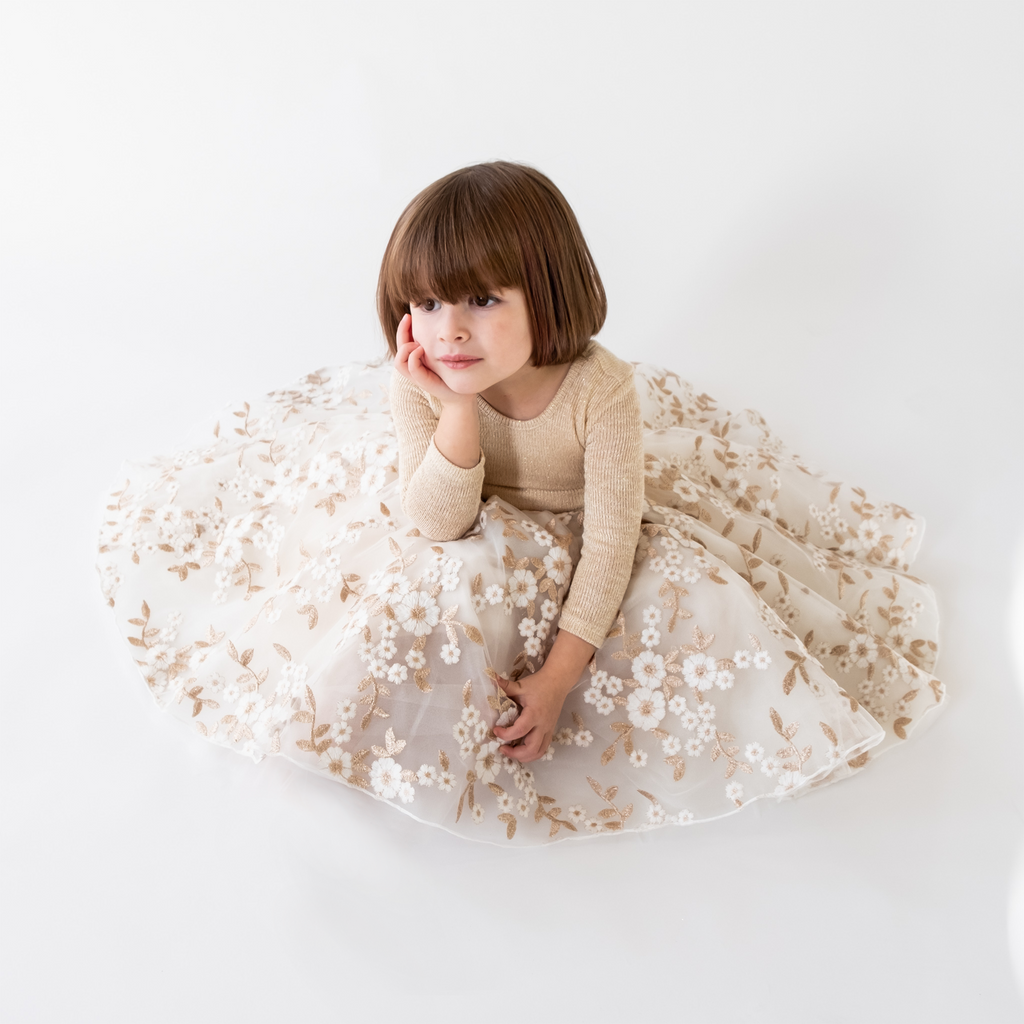 A child looking into the sun wearing the gold tinsel tulle dress