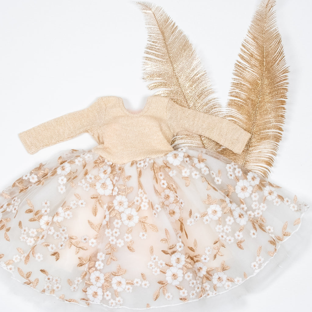 The gold tinsel tulle dress laid on top of gold feathers