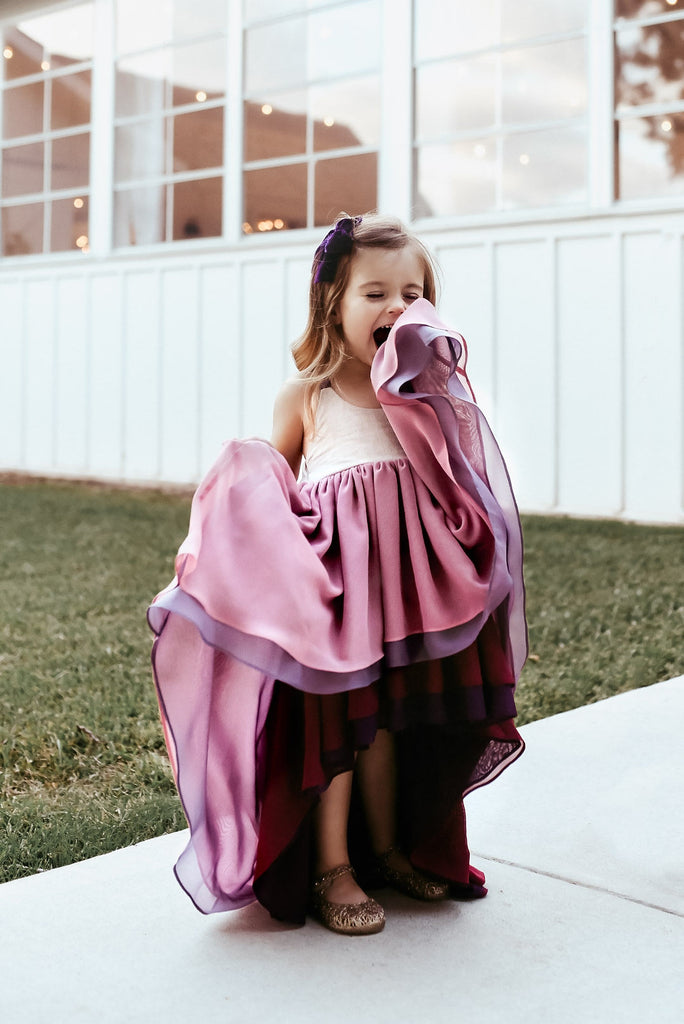 A child posing and singing wearing the winterberry chiffon dress