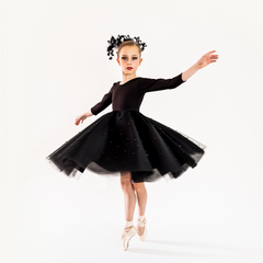 A point ballerina twirling in the black swan dress