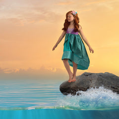 A child standing on a rock in the middle of the ocean singing to all of the sea creatures. She is wearing the mermaid princess dress