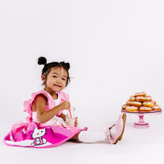 Child sitting with a try of cookies wearing the pink hello kitty belle