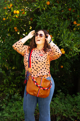 Melissa McCarthy wearing our The Salmon Jaguar Sweatshirt and Moyen Messenger From the Collaboration