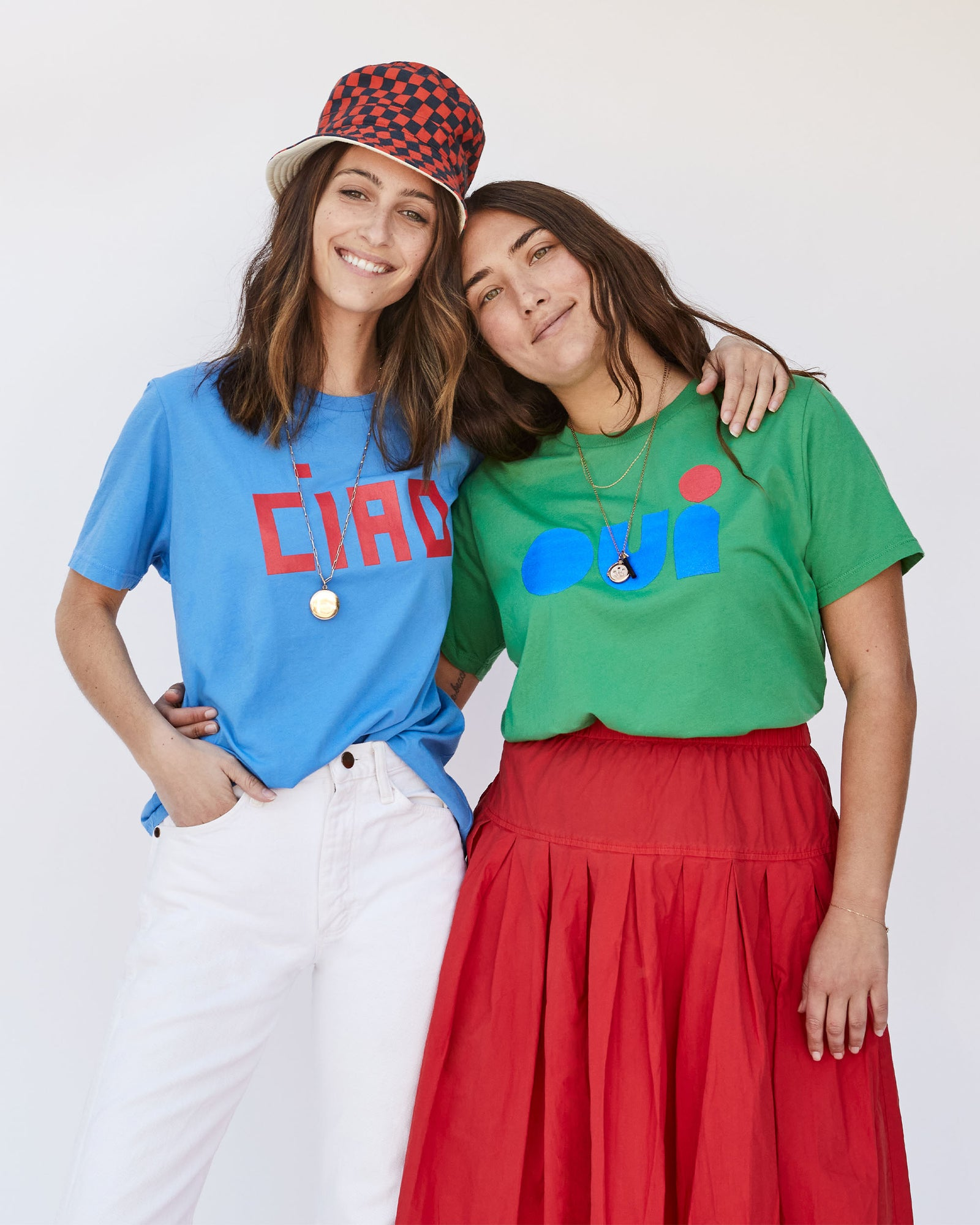 Franny wearing our Camp Fit Blue Ciao Tee and Abbi wearing our Original Fit Green Oui Tee