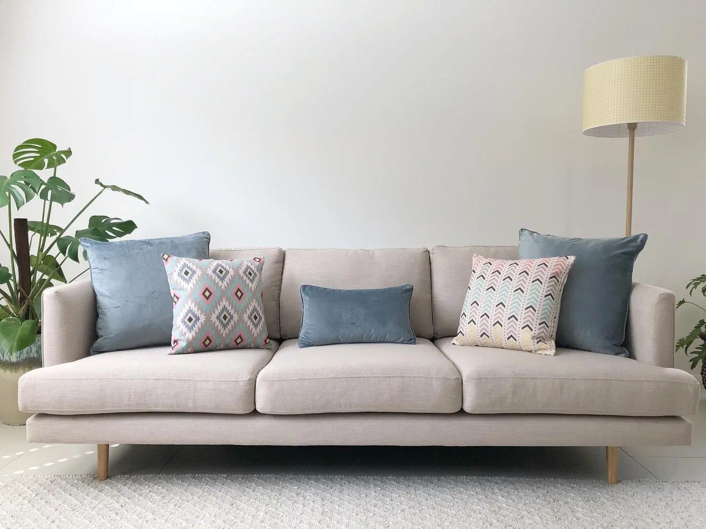 A beige sofa with five decorative cushions in various shades and patterns