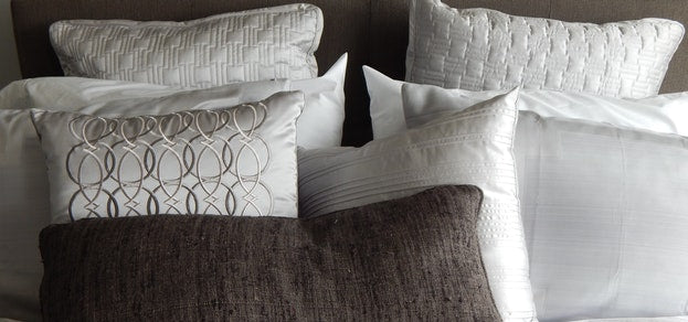 Grey cushion on white bedding