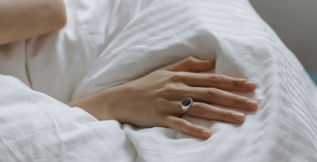 Woman's hand on white bedding