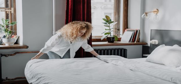 Woman putting crisp white sheets on a bed