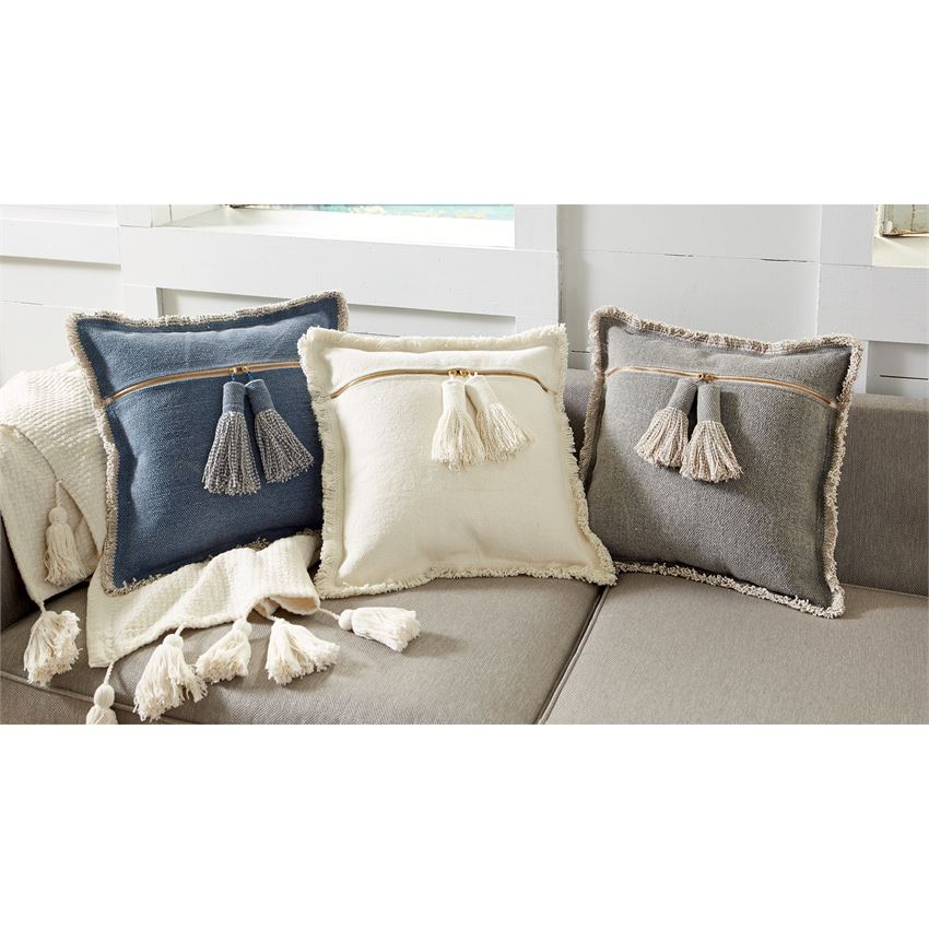 NATURAL DHURRIE TASSEL PILLOW ON BED WITH GRAY AND DENIM COLLRED TASSEL PILLOWS