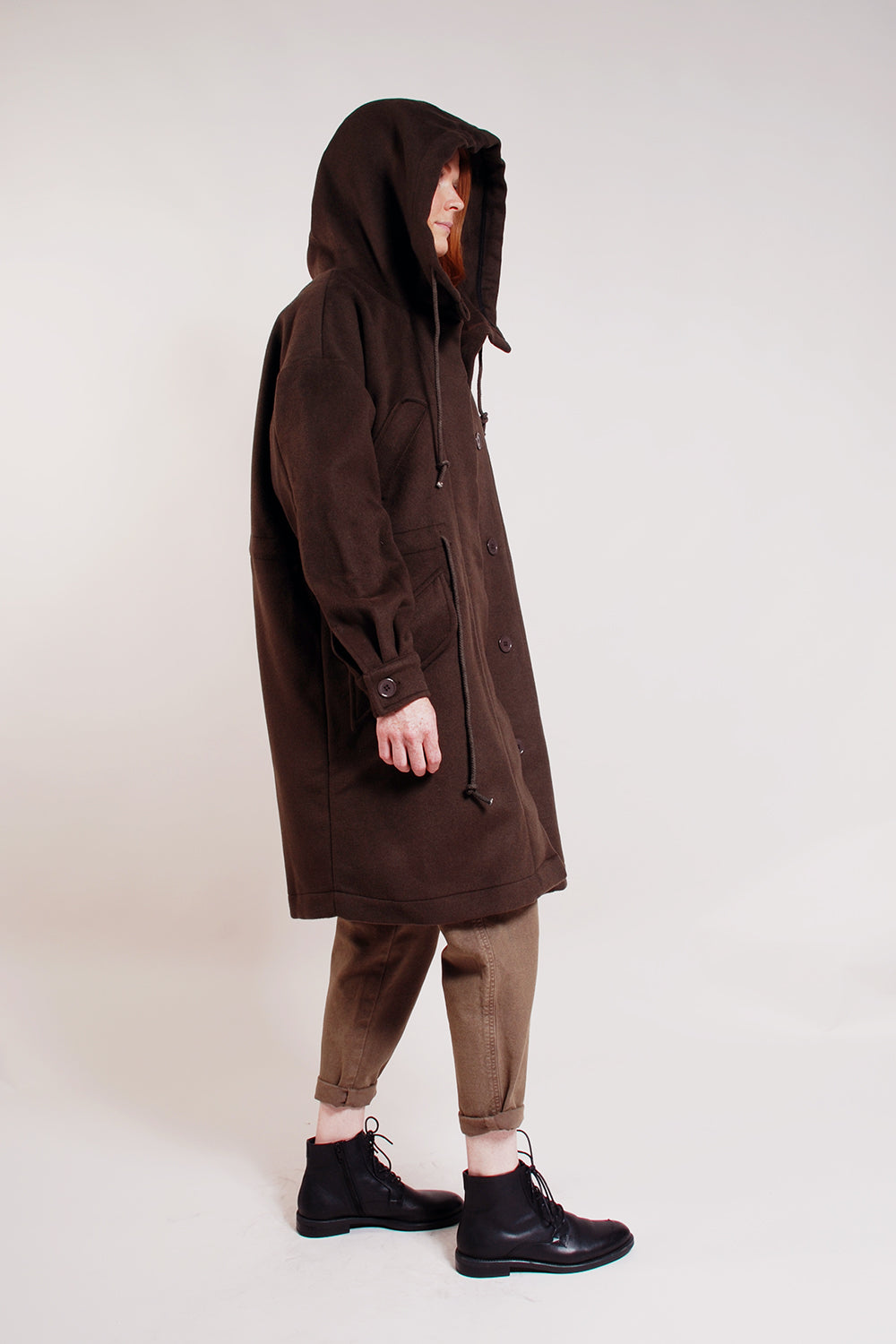 Heavy weight unlined wool parka. Loose fit, knee length, drawstring waist, hidden buttons, large loose hood, handwarmer chest pockets and waist pockets.   96% Wool/ 4% Polyester.