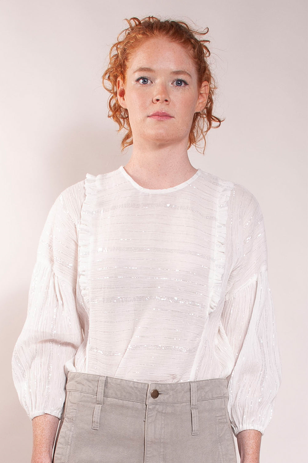 Drop shoulder with gather puff sleeve and elastic cuff. Ruffle detail on front. One button closure in back. Shaped hem. 100% cotton. Natural gauze with silver lurex stripe.